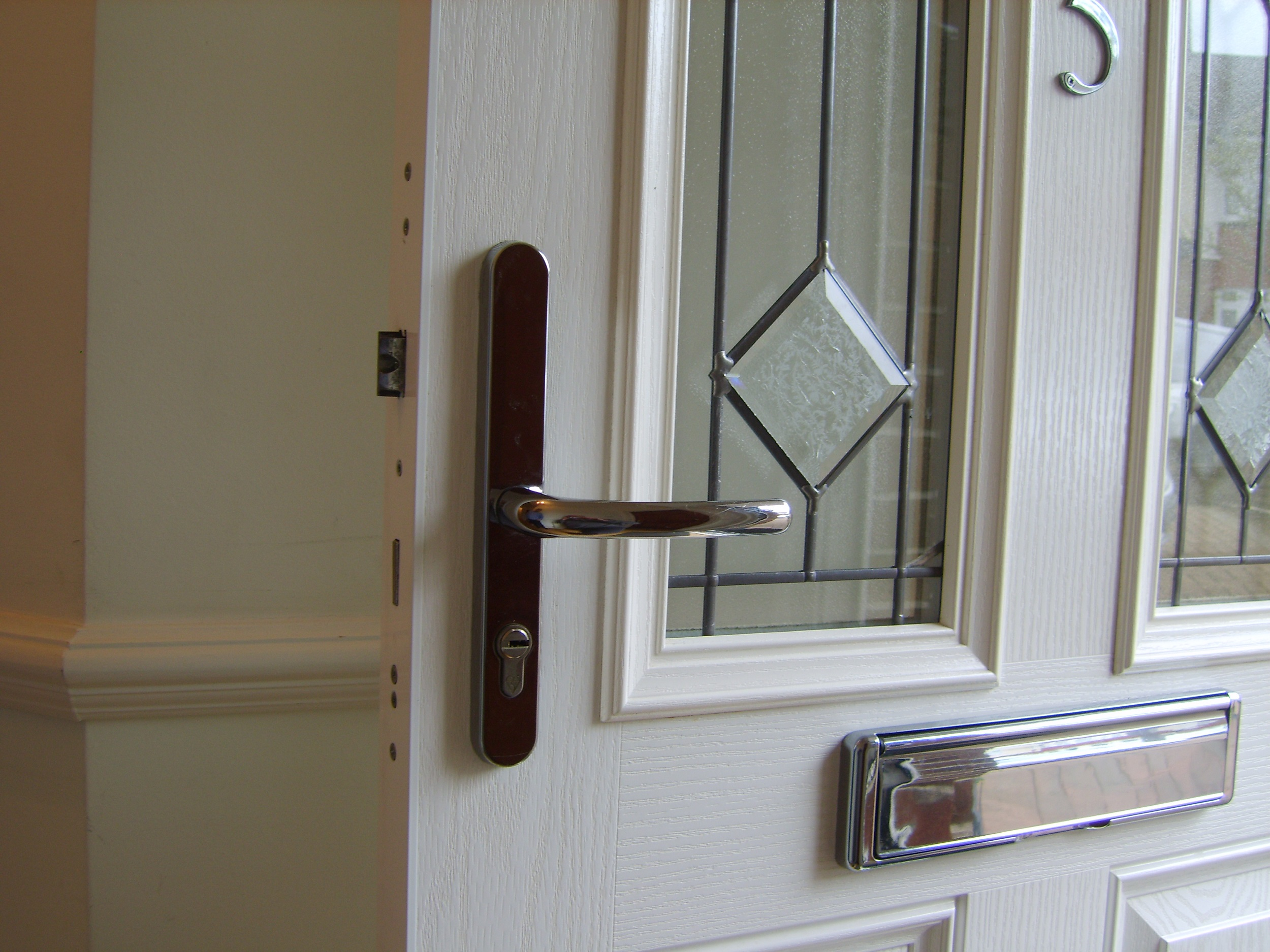 A Multi Point Lock fitted with chrome handles in a partially glazed composite door